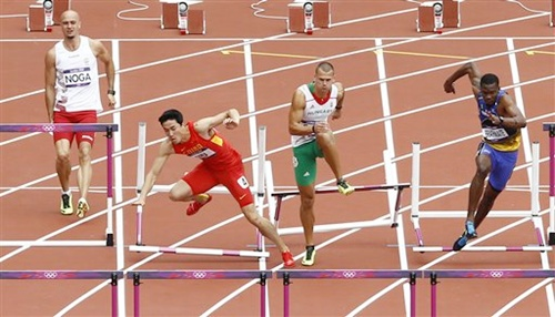 China's Liu Xiang, second left, falls as Hungary's Balazs Baji, Poland's Artur Noga and Barbados' Shane Brathwaite react during a men's 110-meter hurdles heat