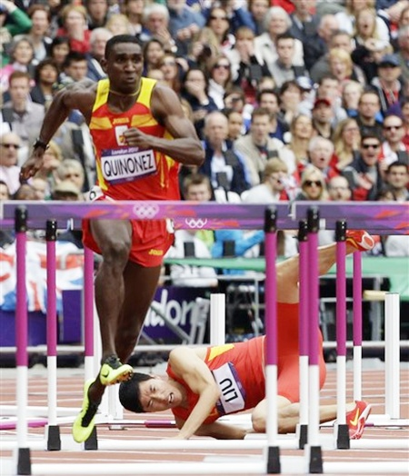 Liu Xiang, right, fails to clear a hurdle
