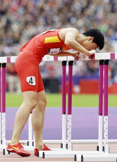 China's Liu Xiang kisses a hurdle as he hops to the finish line after he failed to clear a hurdle and injured himself