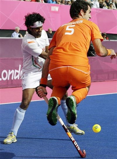 The Netherlands' Marcel Balkestein leaps out of the way as India's Shivendra Singh   moves toward the goal