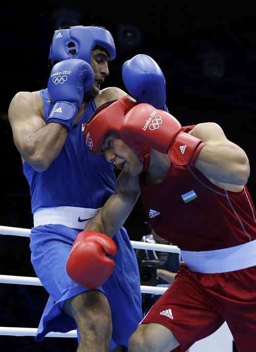 Uzbekistan's Abbos Atoev, right, fights India's Vijender in a middleweight 75-kg quarterfinal boxing match