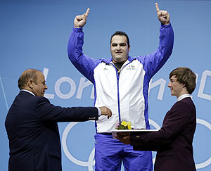 Gold medalist Behdad Salimikordasiabi of Iran on the podium after winning the men's over 105-kg, group A, weightlifting competition on Tuesday