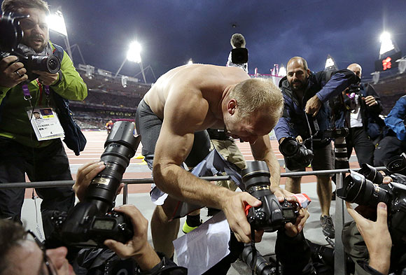 Germany's Robert Harting grabs a photographer's camera as he celebrates his win in the men's discus throw on Tuesday