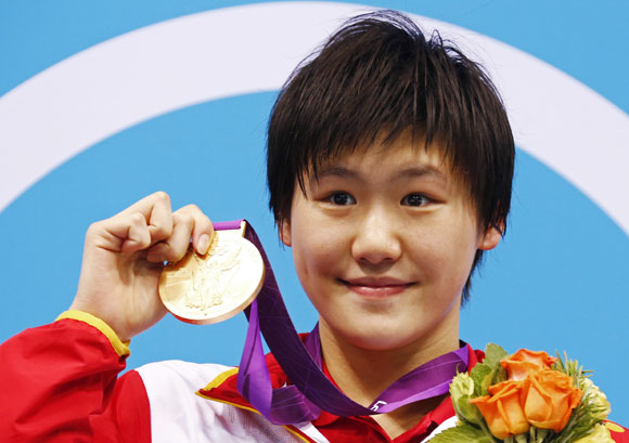 China's Ye Shiwen poses with her gold medal on the podium during the women's 400m individual medley