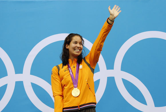 Ranomi Kromowidjojo of the Netherlands waves after she received her gold medal during the women's 100m freestyle victory ceremony