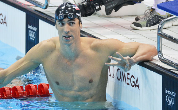 Michael Phelps of the U.S. holds up three fingers after winning the men's 200m individual medley final
