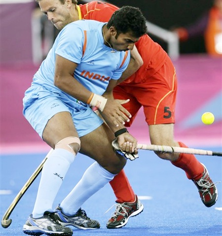 Belgium's Jerome Dekeyser (5) and India's VR Raghunath battle for ball possession