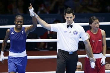 The referee raises Nicola Adams's hand after the semi-final against Mary Kom