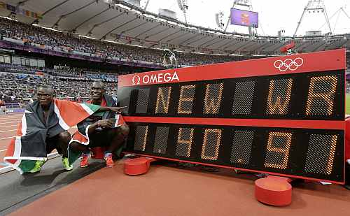 Kenya's David Lekuta Rudisha, right, and Kenya's Timothy Kitum pose next to a next to a timing board displaying Rudisha's new world record in the men's 800-meter final of 1:40.91 during the athletics
