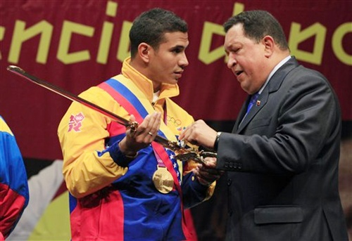 Venezuela's President Hugo Chavez, right, presents a replica of a sword once used by   South American independence hero Simon Bolivar to Venezuela's fencer Ruben Limardo