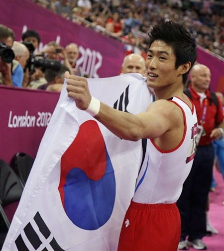 South Korean gymnast Yang Hak-seon holds his national flag