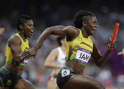 Jamaica's Kerron Stewart gets the baton from her teammate Schillonie Calvert, left, in a women's 4x100-meter relay