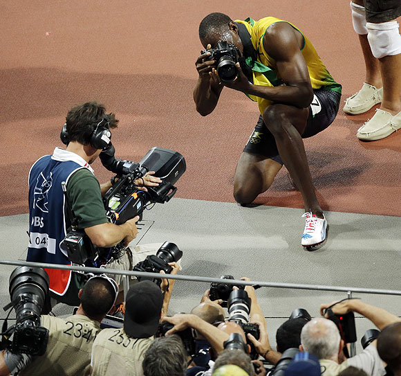 Jamaica's Usain Bolt uses a photographers camera as he takes pictures after winning the gold medal in the men's 200m on Thursday