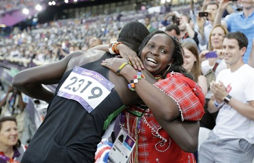 Kenya's David Lekuta Rudisha, left, hugs his wife Lizzy