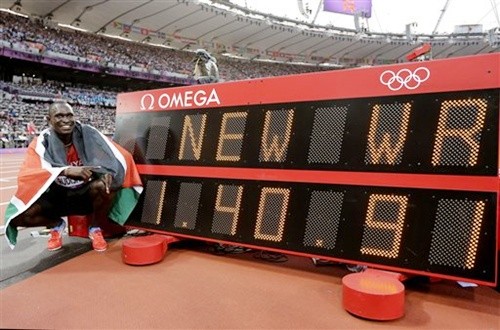 Kenya's David Lekuta Rudisha poses next to a timing board displaying his new world record