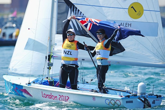 Jo Aleh (black cap) and Olivia Powrie (white cap) of New Zealand celebrate finishing first and winning gold medal in the 470 Women's Class Sailing