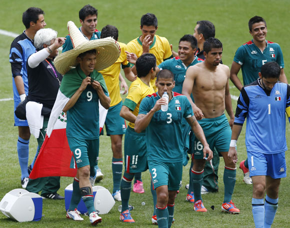 Mexico's double goalscorer Oribe Peralta (front L) wears a sombrero hat and a national flag while celebrating with team mates after their victory over Brazil in their men's soccer final