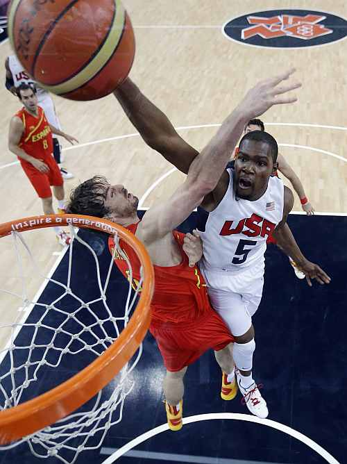 United States' Kevin Durant (5) slam dunks to score over Spain's Pau Gasol, left, during the Men's Basketball Gold medal game between the United States and Spain
