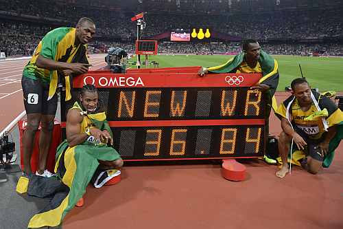 Usain Bolt, Yohan Blake, Michael Frater and Nesta Carter of Jamaica celebrate next to the clock after winning gold and setting a new world record of 36.84 during the Men's 4 x 100m Relay Final