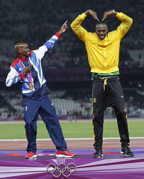 Jamaica's Bolt celebrates with Britain's Farah on the podium after each receiving gold medals, Bolt for men's 4x100m relay and Farah for men's 5000m at the victory ceremony