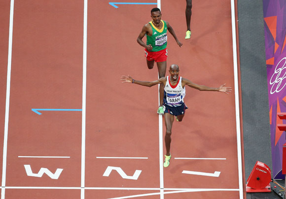 Mohamed Farah of Great Britain crosses the finish line to win gold ahead of Dejen Gebremeskel of Ethiopia in the Men's 5000m Final