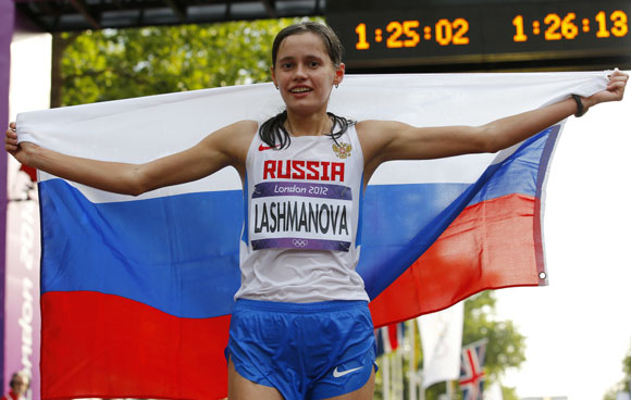 Russia's Elena Lashmanova holds her national flag as she celebrates after winning the women's 20km race walk final