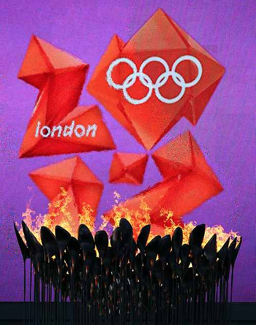 The Olympic Cauldron burns in front of the London 2012 logo