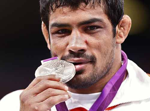 India's Sushil Kumar poses with his silver medal at the podium of the Men's 66Kg Freestyle wrestling