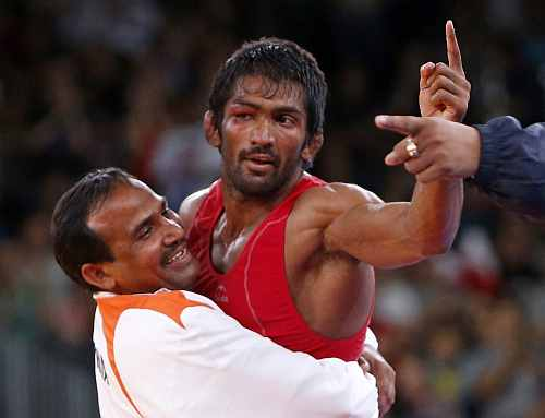 India's Yogeshwar Dutt (in red) reacts after defeating for the bronze medal North Korea's Jong Myong Ri