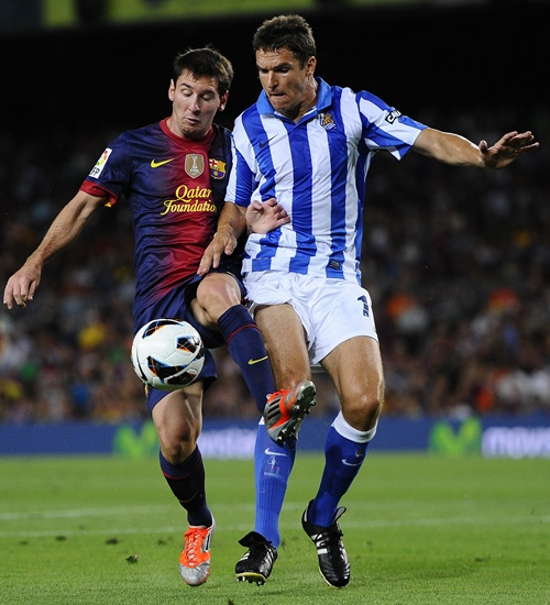 Lionel Messi of FC Barcelona (left) duels for the ball with Ion Ansotegi Gorostola of Real   Sociedad
