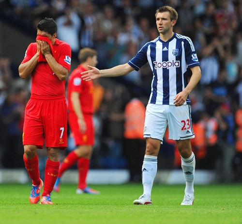 Luis Suarez of Liverpool is consoled by Gareth McAuley of West Brom
