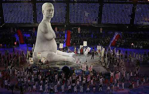Performers hold placards next to giant statue as they take part at opening ceremony of London 2012 Paralympic Games in Olympic Stadium