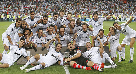Real Madrid's players celebrate with the trophy after winning their Spanish Super Cup second leg match against Barcelona at the Santiago Bernabeu stadium on Wednesday