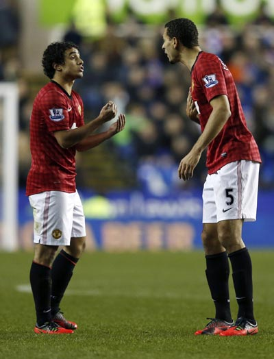 Manchester United's Rafael (L) speaks to to team mate Rio Ferdinand during their English Premier League soccer match against Reading at the Madejski Stadium in Reading