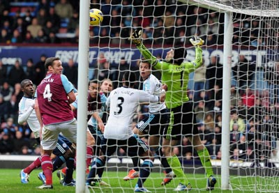 Petr Cech of Chelsea saves from the headed of Winston Reid of West Ham United during the Barclays Premier League match between West Ham United and Chelsea at the Boleyn Ground