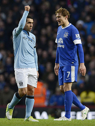 Manchester City's Carlos Tevez (left) celebrates after scoring as Everton's Nikica Jelavic looks on during their English Premier League match on Saturday