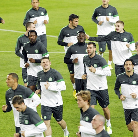 Celtic's players warm up during a training session
