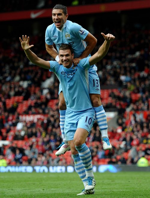 Edin Dzeko of Manchester City celebrates scoring his team's sixth goal with team mate Aleksandar Kolarov