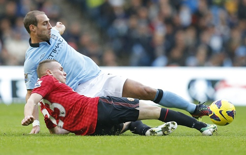 Manchester City's Pablo Zabaleta (top) challenges Manchester United's Tom Cleverley