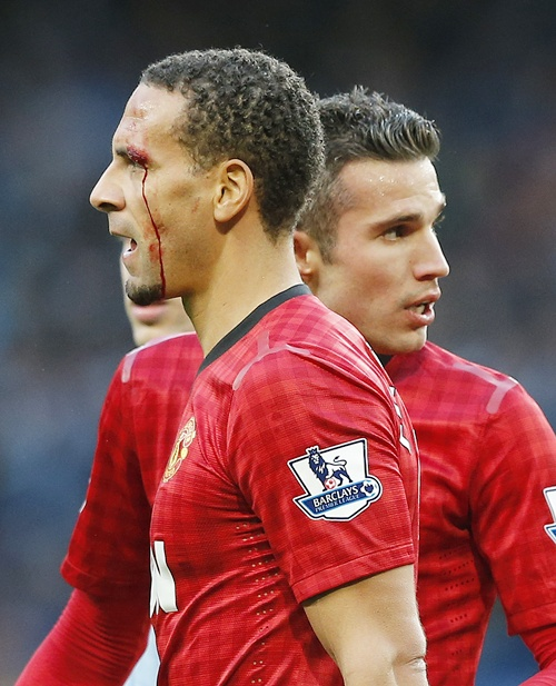 Manchester United's Rio Ferdinand (left) is helped from the pitch by teammate Robin van Persie