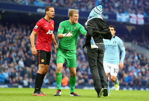 Joe Hart of Manchester City confronts a pitch invader