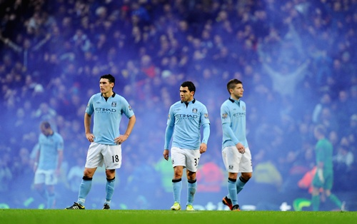 Carlos Tevez of Manchester City and team-mate Gareth Barry look dejected