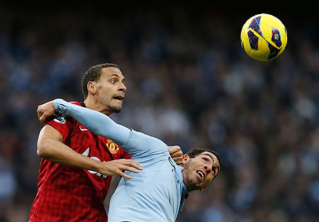 Manchester City's Carlos Tevez (right) challenges Manchester United's Rio Ferdinand on Sunday