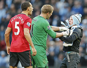 Manchester City's Joe Hart (centre) prevents supporter Matthew Stott from reaching Manchester United's Rio Ferdinand (left) after the latter was struck by an object thrown from the crowd during the Manchester derby on Sunday