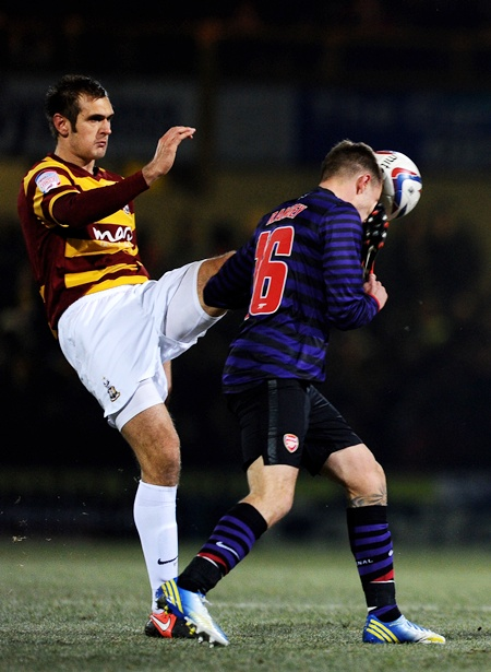 James Hanson of Bradford makes contact with the face of Aaron Ramsey of Arsenal