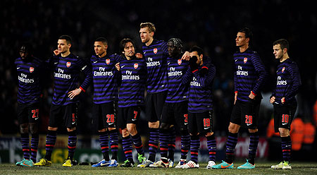 A dejected Arsenal team look on as they head out of the competition in the penalty shootout