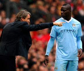 Manchester City manager Roberto Mancini speaks to Mario Balotelli
