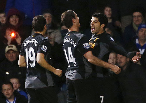 Liverpool's Luis Suarez (right) celebrates with teammates after scoring against Queens Park Rangers during their English Premier League match on Sunday