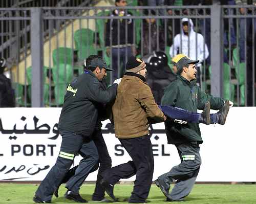 Medical personnel carry a wounded soccer fan at Port Said Stadium