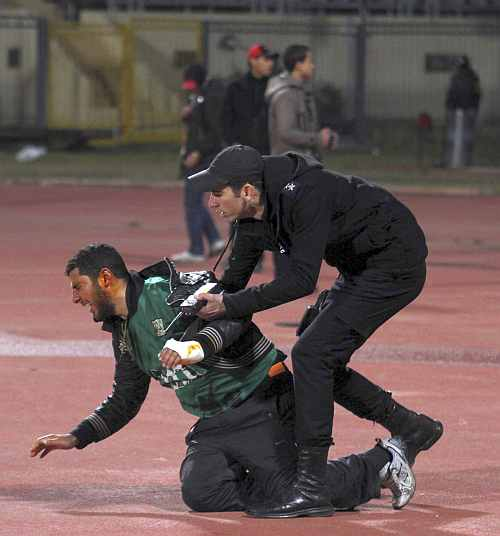 A policeman arrests an injured rioting soccer fan as chaos erupts at a soccer stadium in Port Said city